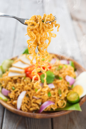 Spicy fried curry instant noodles or Malaysian style maggi goreng mamak photo