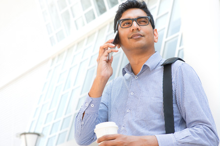 Young Asian Indian businessman on the phone with a cup of coffee in morning photo