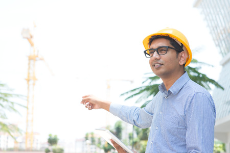 Portrait of a smiling Indian male contractor engineer with hard hat pointing to a construction site photo
