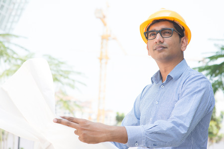 Portrait of a 30s Indian male site contractor engineer with hard hat holding blue print paper at construction site. photo
