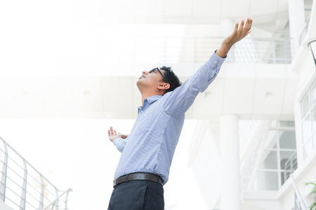 Successful Asian Indian businessman with arms outstretched celebrating his victory photo
