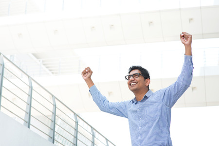 Successful Asian Indian businessman with arms up celebrating his victory photo