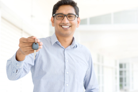 passing over: Young Asian Indian estate agent or salesman showing a key