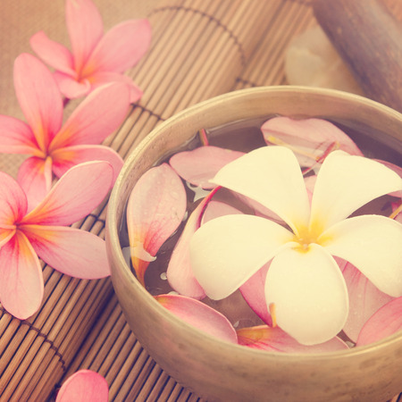 Frangipani, hot and cold stone on bamboo mat. photo