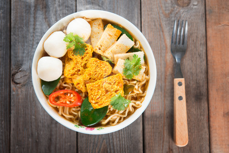 instant noodle: Spicy curry instant noodles soup with fork on wooden dining table Stock Photo