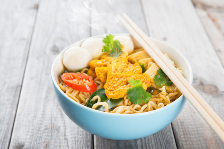thai noodle soup: Spicy curry instant noodles soup with chopsticks on wooden dining table Stock Photo