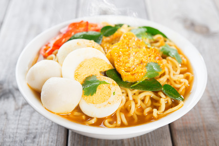 cooked instant noodle: Spicy curry instant noodles soup on wooden dining table