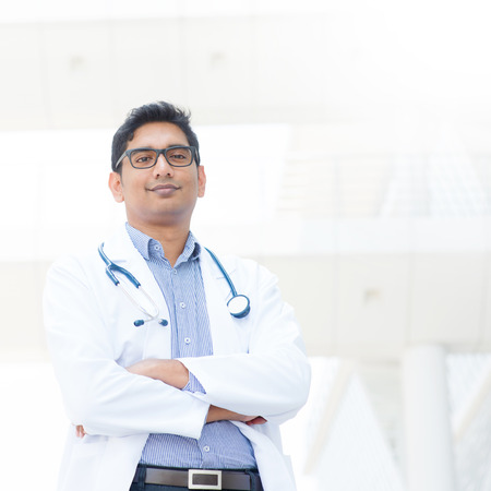 Portrait of a smiling Asian Indian male medical doctor in lab uniform standing in front of hospital.