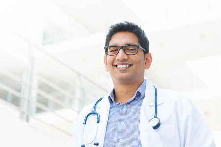 Portrait of a smiling Asian Indian male medical doctor in uniform, hospital building at background. Stock Photo