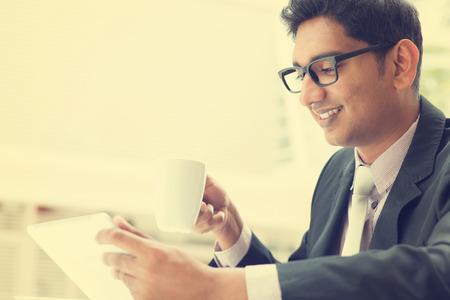 office break: Hombre de negocios indio joven asi�tica con un tablet PC durante las vacaciones de la oficina en el caf�, relajarse con una taza de caf�. India hombre de negocios, en el estilo retro de la vendimia.