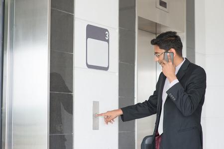 Hombre de negocios indio asiático presionando el botón del ascensor, puerta esperando abierta para entrar en el interior del ascensor. Foto de archivo