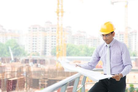 Portret van een glimlachende Aziatische Indiase man aannemer ingenieur met hoed lezen blauwdruk op bouwplaats hard.