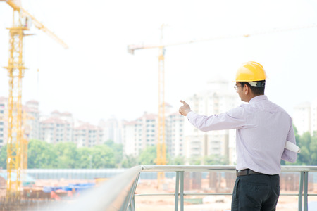 Portrait of a smiling Asian Indian male contractor engineer with hard hat pointing to construction site. Stock Photo