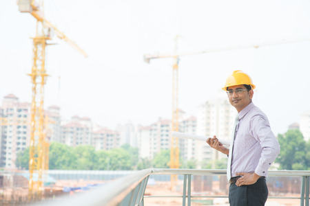 Portrait of a smiling Asian Indian male contractor engineer with hard hat standing at construction site. photo