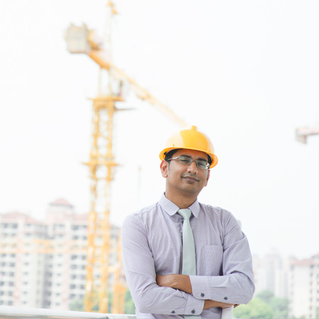 Portrait of a smiling Asian Indian male contractor engineer with hard hat standing in front construction site. Stock Photo