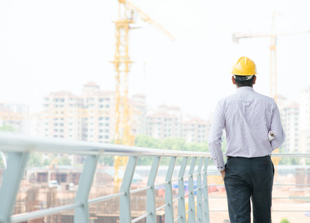 Rear view of a Asian Indian male contractor engineer with hard hat standing in front construction site, inspecting the progress. photo