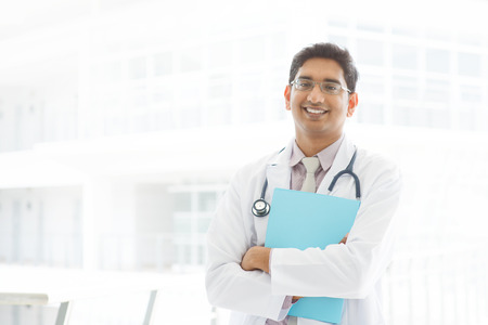 Portrait of a smiling Asian Indian male medical doctor standing inside hospital, holding file folder.