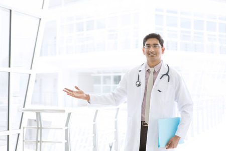 Portrait of a smiling Asian Indian male medical doctor standing inside hospital, holding file folder and showing welcome hand sign.