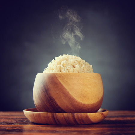 Cooked organic basmati brown rice in wooden bowl with hot steam smoke on dining table