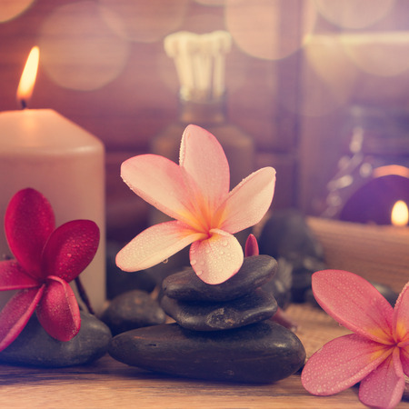 Spa setting with frangipani flower, essential oil, zen stones and aromatic candles on table, Zen concept in vintage retro style. photo