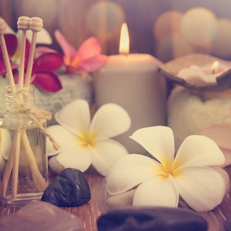 Concetto di wellness e spa con candele, fiore del frangipani, legno di sandalo e bastoni in rattan sul lettino da massaggio in stile retrò vintage.