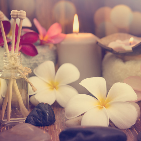 bali massage: Wellness and spa concept with candles, frangipani flower, sandalwood and rattan sticks on massage table in vintage retro style. Stock Photo