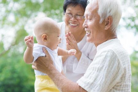 внук: Счастливые азиатские бабушки и дедушки играют с ребенком внука в саду на открытом воздухе.