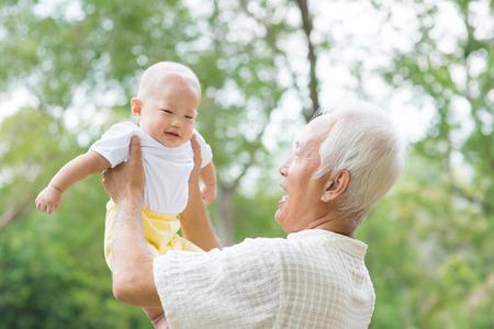 Asian Chinese dědeček a vnuk baví na venkovní zahrádce.