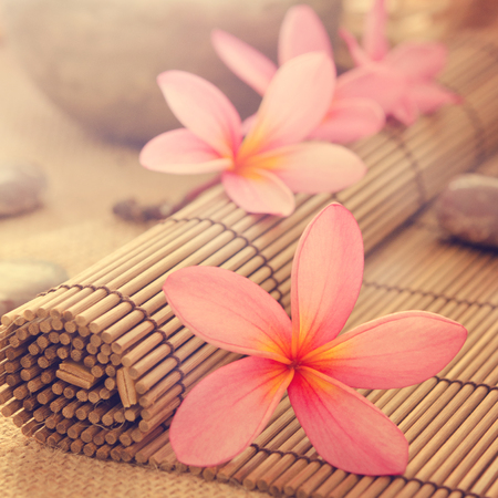 Health spa setting, low light with ambient. Frangipani, hot and cold stone on bamboo mat in vintage retro style. photo