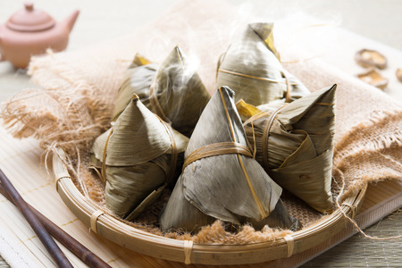 Asian Chinese rice dumplings on basket, tea at background. Stock Photo