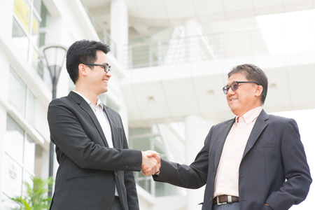 talking businessman: Asian businessmen handshaking. Senior CEO hand shake with young executive.