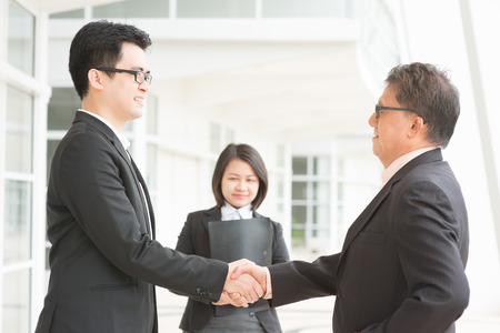 Business deal, Asian businessmen handshaking. Senior CEO hand shake with young executive.  photo