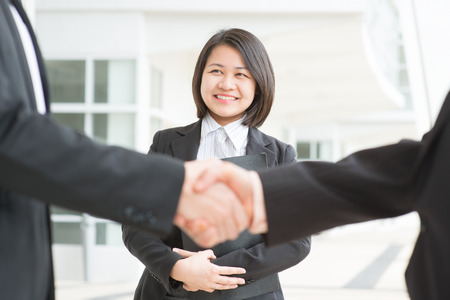 Business deal, Asian businessmen handshaking. Focus on assistant or secretary.