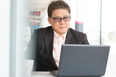 asian elderly: Asian Chinese CEO boss using internet with laptop at cafe. Senior male businessman.