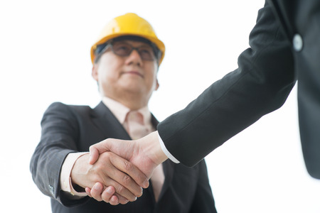 Senior male architects with hardhat hand shaking. photo