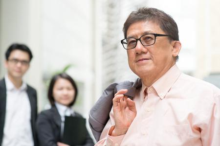 Líder y miembro del equipo. Retrato de 60s asiática jefe CEO chino sonrientes. Negocios de alto nivel y el personal masculino, moderno edificio de oficinas de bienes como fondo. Foto de archivo