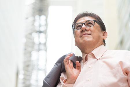 Portret van de jaren '60 Aziatische Chinese CEO baas lacht en kijkt weg. Senior mannelijke zakenman, echt modern kantoorgebouw als achtergrond. Stockfoto