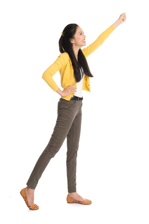 Full body Asian woman standing with hand raised high grabbing something, isolated on white background. photo