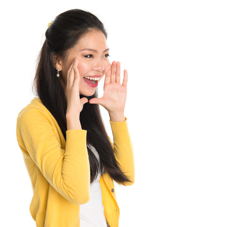 pan asian: Young Asian girl shouting loud, hands next to the mouth, isolated on white background