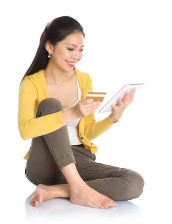 Southeast Asian woman online shopping, hands holding credit card and digital computer tablet sitting at floor. Full body isolated on white background. photo