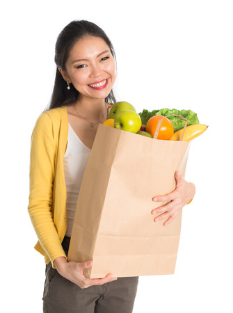 Happy smiling young pan Asian woman holding paper shopping bag full of groceries isolated on white background. Stock Photo