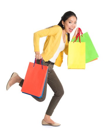 Full body Asian woman running with shopping bags, isolated on white background. photo