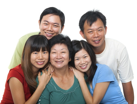 adults offspring: Asian family portrait. Happy senior mother and her adult offspring, smiling isolated on white .