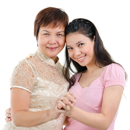 pan asian: Mixed race Asian family portrait. Elderly mother and adult daughter holding hands bonding isolated on white .
