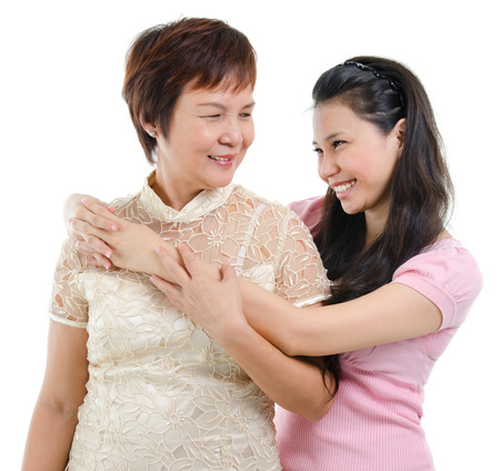 pan asian: Adult daughter embraces mother isolated on white . Mixed race Asian family portrait.  Stock Photo