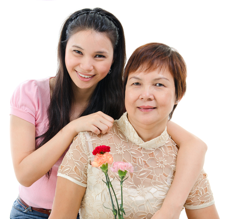 Senior mother holding carnation flower, adult daughter embraces mom, isolated on white . Mixed race Asian family portrait.  photo