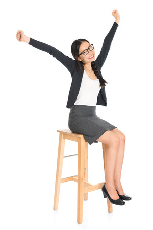 arms on chair: Full body Asian business executive seated on chair, arms raised celebrating success isolated white . Chinese girl model.