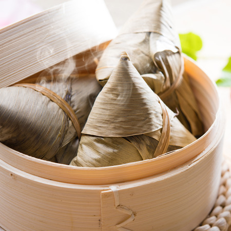 Hot rice dumpling or zongzi. Traditional steamed sticky glutinous rice dumplings. Chinese food dim sum. Asian cuisine. photo