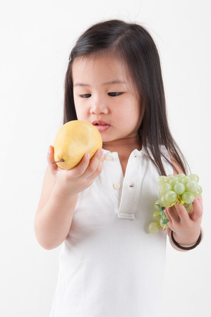 Child eats fruit. Little Asian girl eating pear and grapes, isolated on white  photo