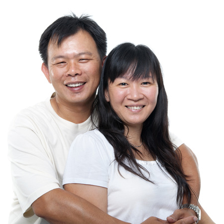 Happy southeast Asian mature couple hugging and smiling, isolated on white .